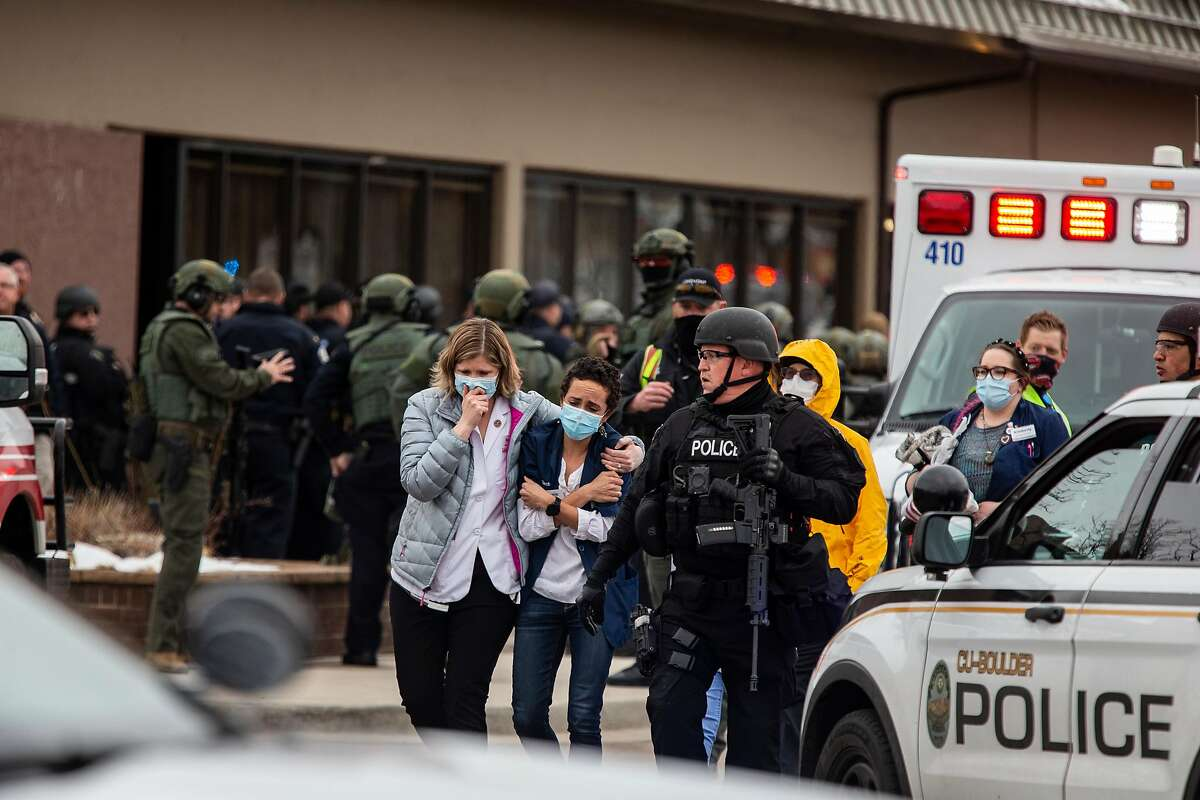 BOULDER, CO - MARCH 22: Healthcare workers walk out of a King Sooper's Grocery store after a gunman opened fire on March 22, 2021 in Boulder, Colorado. Dozens of police responded to the afternoon shooting in which at least one witness described three people who appeared to be wounded, according to published reports. (Photo by Chet Strange/Getty Images))