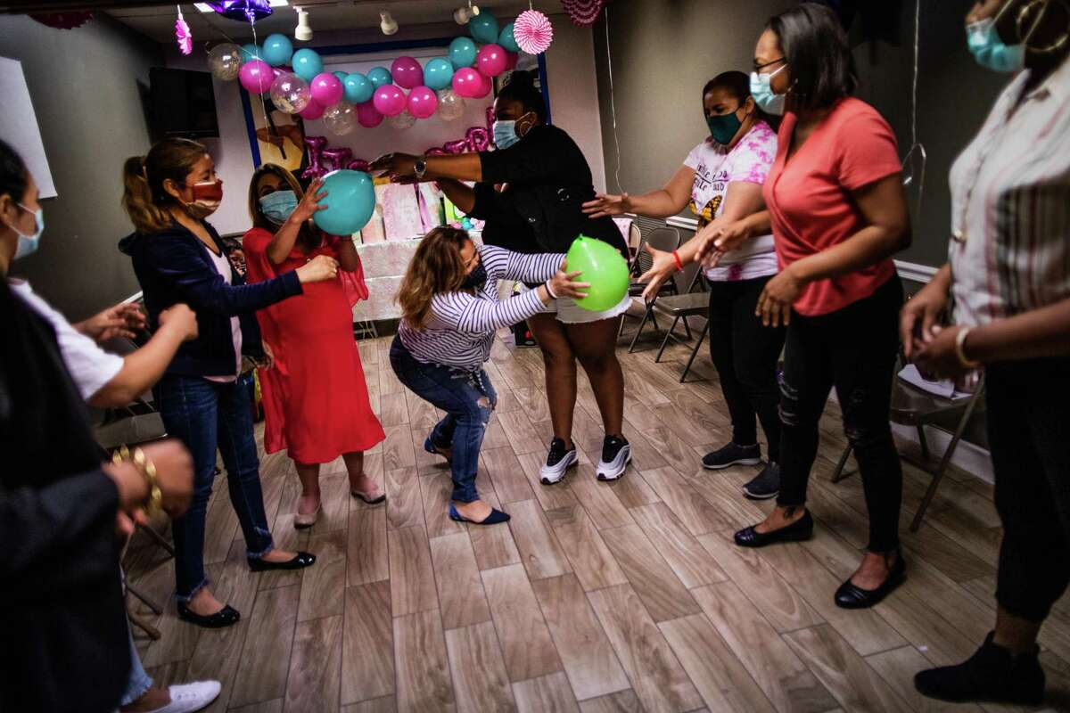 Esmeralda Joya, center, 48, passes a balloon during a team building game for immigrant women.