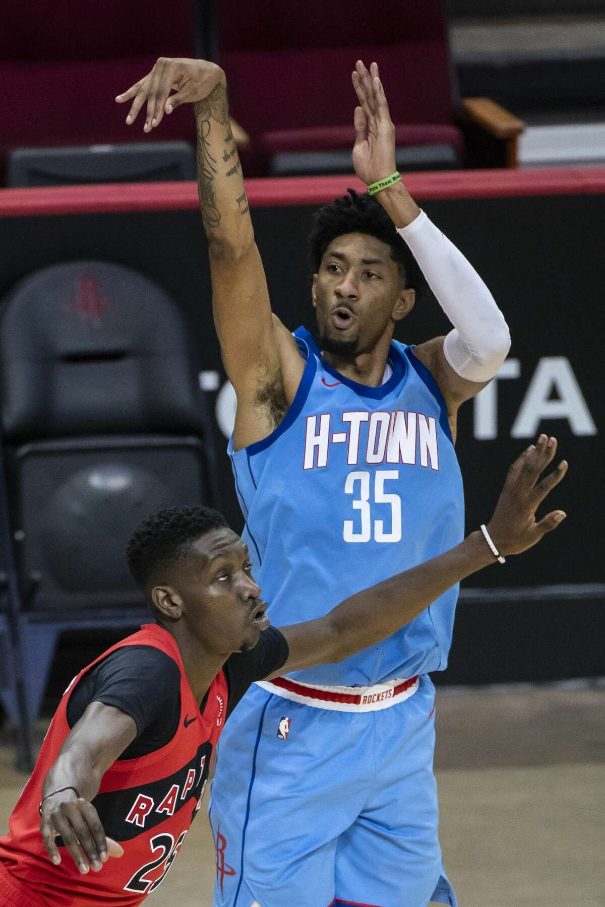 Houston Rockets center Christian Wood (35) shoots a three point shot over Toronto Raptors forward Chris Boucher (25) during the third quarter of an NBA game between the Houston Rockets and Toronto Raptors on Monday, March 22, 2021, at Toyota Center in Houston.