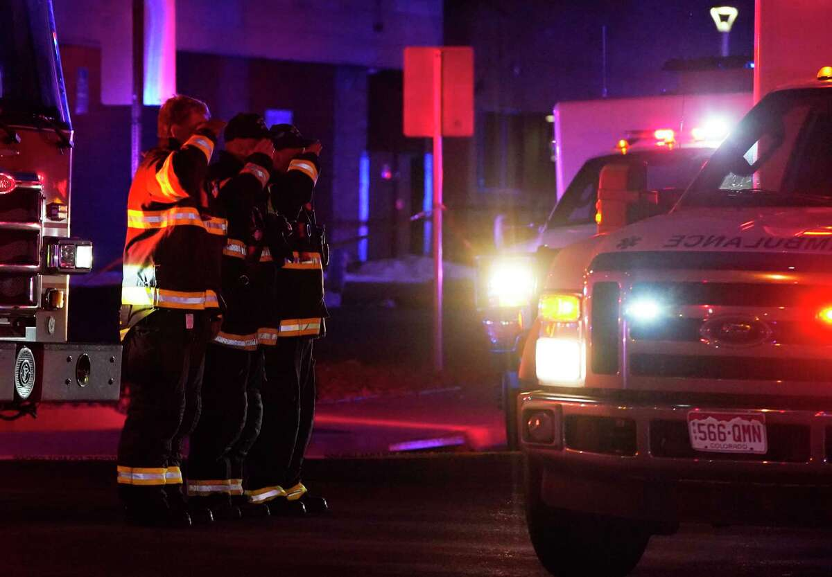 Firefighters salute an ambulance as it leaves a King Soopers grocery store where authorities say multiple people have been killed in a shooting, Monday, March 22, 2021, in Boulder, Colo.