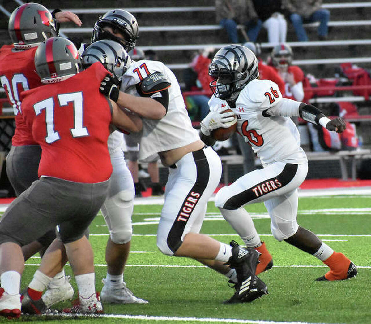 Edwardsville running back Justin Johnson Jr. looks for room behind the blocking of Alex Vaston (No. 77) in the first quarter of Friday's game against Alton.