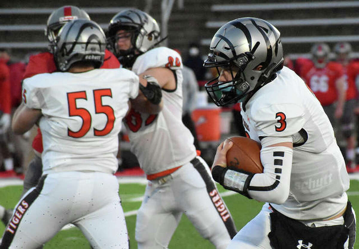 Edwardsville quarterback Ryan Hampton finds space as Austin Wolfe (No. 55) and Pierce Boyer (No. 89) block an Alton defensive lineman during Friday's game.