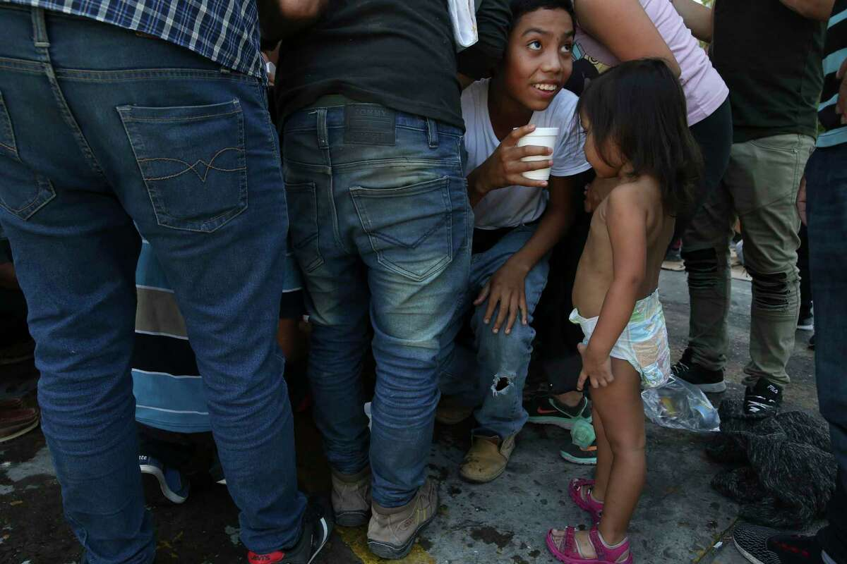 Honduran Rosbin Vasquez, 13, gets a cup of lemonade as migrants crowd around jugs offered by religious volunteers at the Mexican Immigration offices by International Bridge No. 1 in Nuevo Laredo, Mexico on Thursday, Aug. 15, 2019. Mostly Central American migrants were sheltered at the place after they crossed into the U.S. seeking asylum but were sent back to Mexico under the Migrant Protection Protocols. They feared kidnappings by cartels operating in the city if they left the area and most wanted to return back to their home countries.