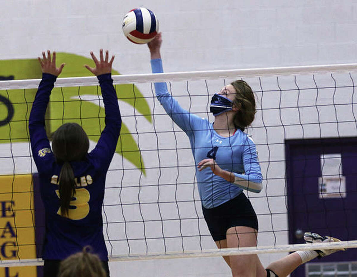 Jersey's Kari Krueger (right) hits past the block by CM's Harper Buhs in the Panthers' season opener last Thursday at Bethalto. The Panthers opened at home Monday night and beat Brussels to even their record at 1-1.