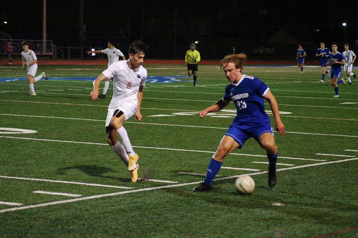 Friendswood's Isaac Logsdon (23) tries to work the ball past Santa Fe's Diego Rabago (6) at Friendswood High School.