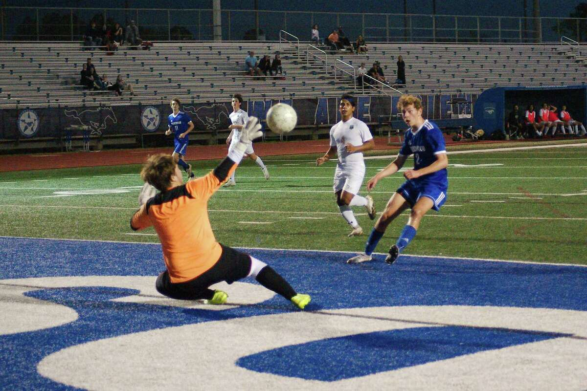 Santa Fe's Caston Kennedy (1) protects the goal as Friendswood's Chris Cooper (2) tries to score in a district soccer game at Friendswood High School.