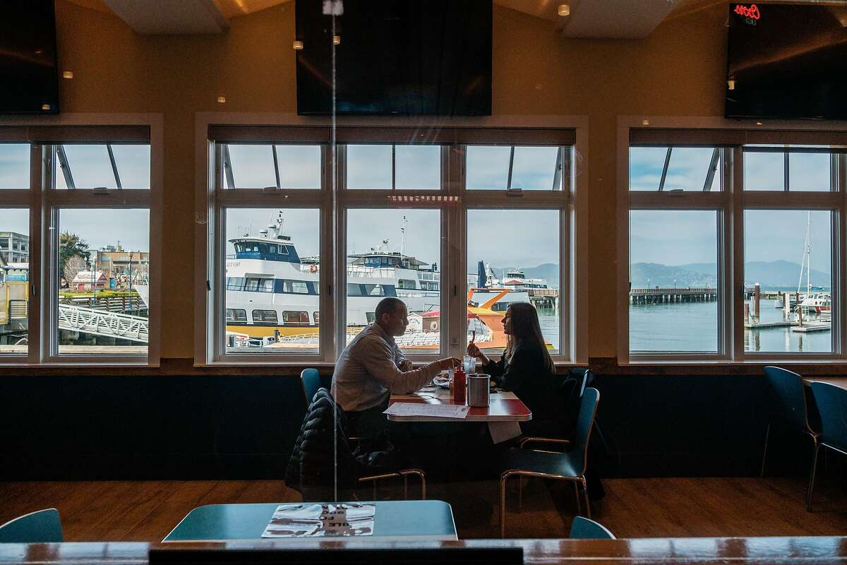 Two people dine indoors at Wipeout on Pier 39 in San Francisco. Health experts recommend vaccinated people still be cautious with indoor dining as more contagious variants spread.