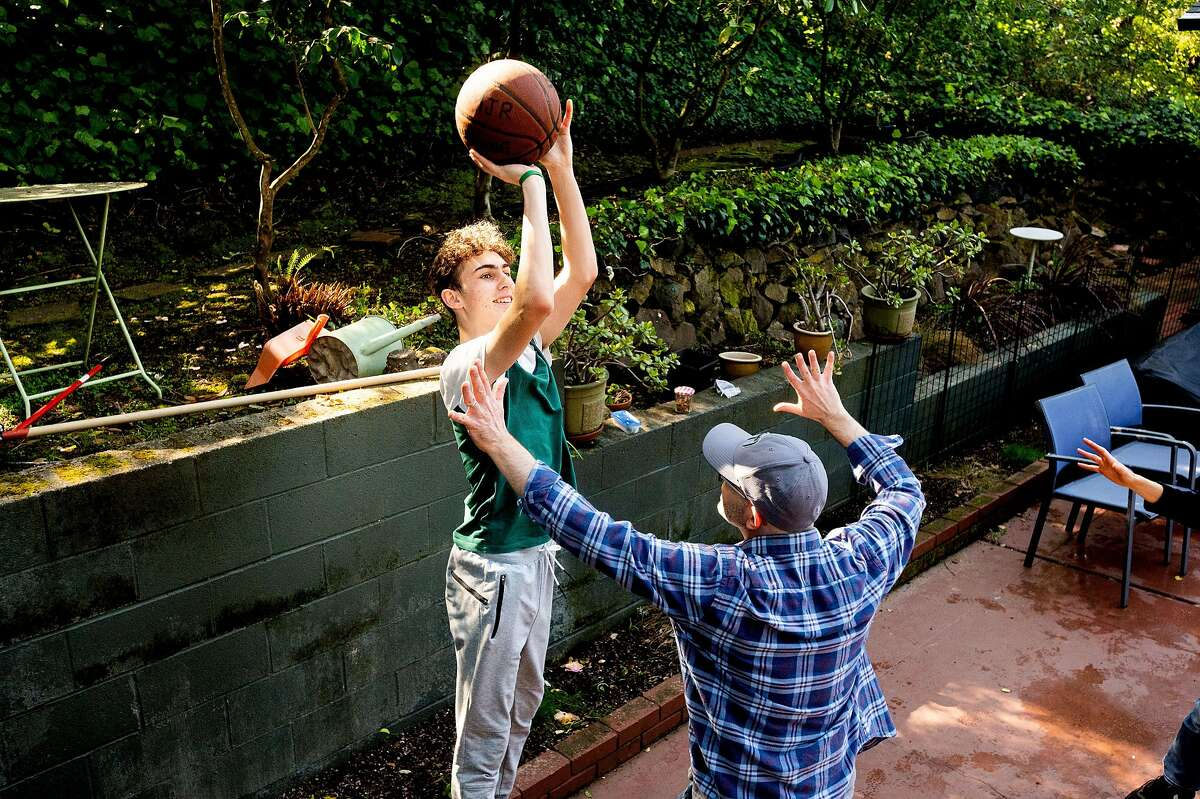 Miles Robinson, 13, plays basketball with dad Steve Robinson in the backyard of their Oakland home in March. The Robinsons plan to send Miles to Camp Tawonga this summer.
