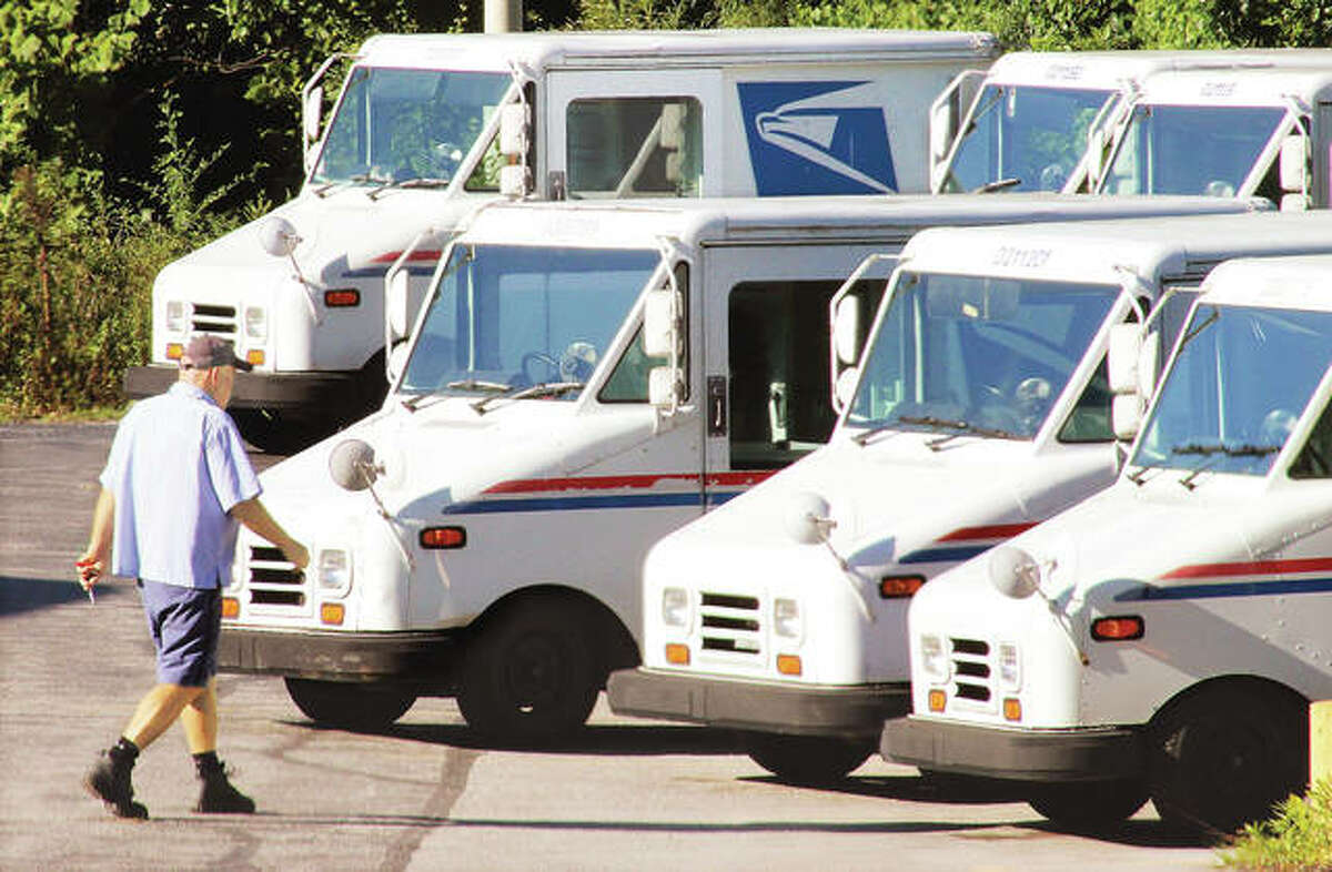 An Alton letter carrier picks up his vehicle behind the main Alton Post Office on the Homer Adams Parkway to load it up for mail delivery on his route. Carriers mostly sort and load their own vehicles before heading out to hand deliver mail, door-to-door everywhere in the country.
