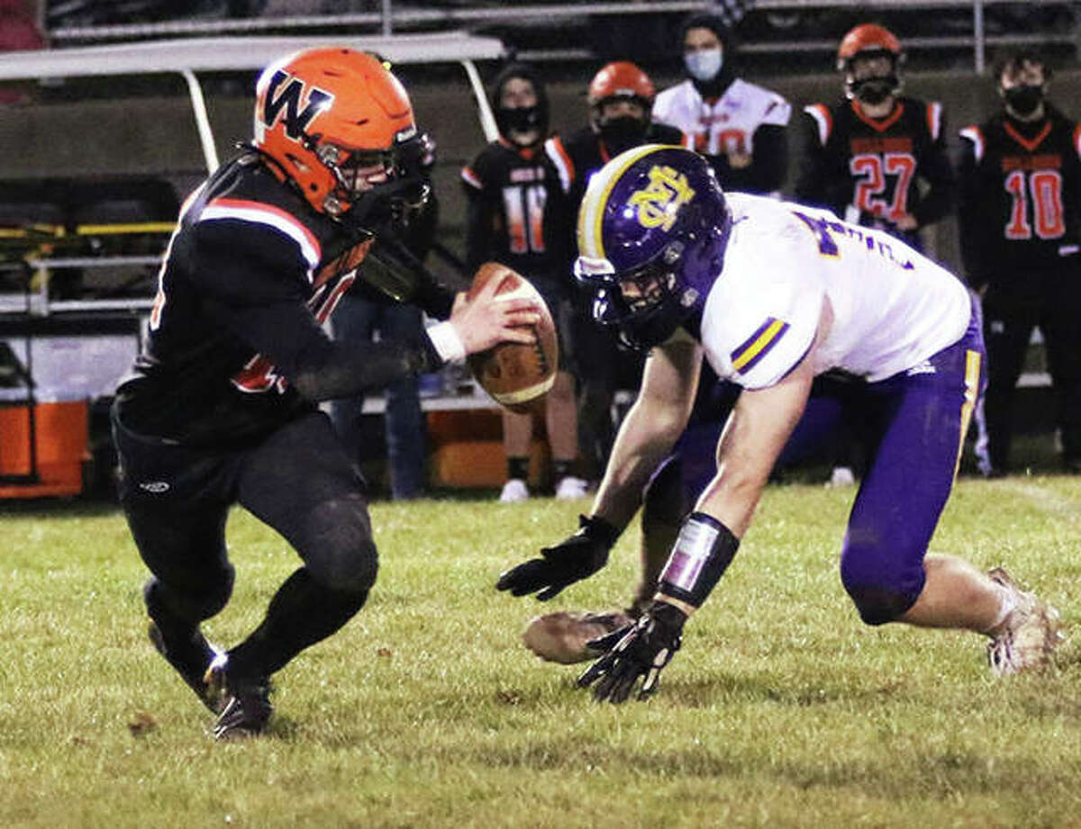 Waterloo QB Eric Brown (left) dries to scramble away from CM pass rusher Vinny Cafazza, but is taken down in the third quarter for one of Cafazza's two sacks on Friday night at Waterloo.