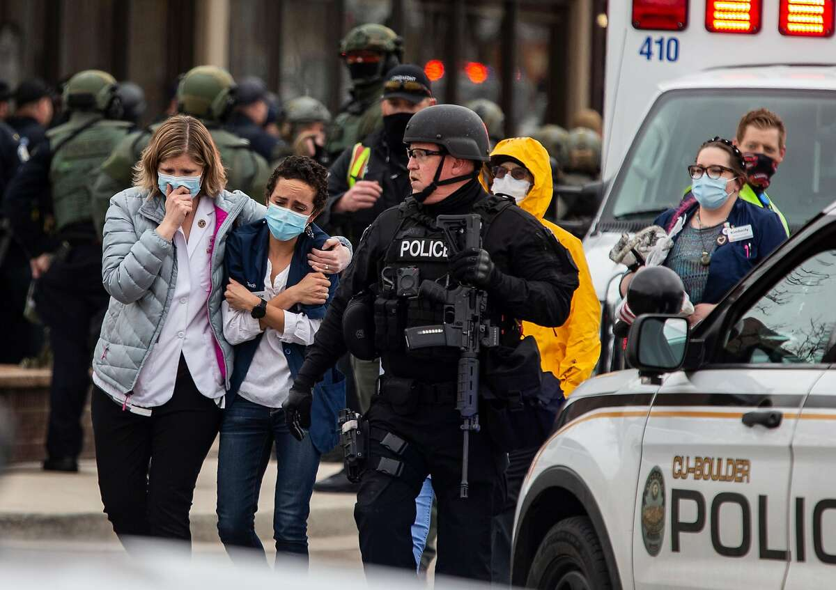 Healthcare workers walk out of a King Sooper's Grocery store after a gunman opened fire on March 22, 2021, in Boulder, Colorado. Dozens of police responded to the afternoon shooting in which at least one witness described three people who appeared to be wounded, according to published reports. (Chet Strange/Getty Images/TNS)