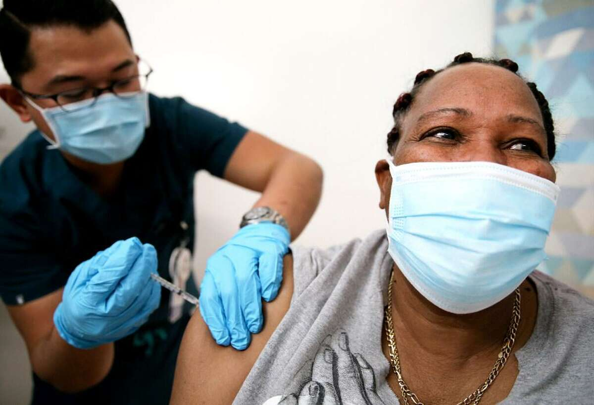 Lorraine Harvey, an in-home care worker, receives her first dose of the COVID-19 vaccine from registered nurse Rudolfo Garcia at a clinic at Martin Luther King Jr. Community Hospital in South Los Angeles on February 25, 2021 in Los Angeles, California. African Americans and Latinos comprise a majority of the South LA community and are dying of COVID-19 at a rate significantly higher than whites. Vaccine equity has also lagged in South Los Angeles relative to some more wealthy areas.