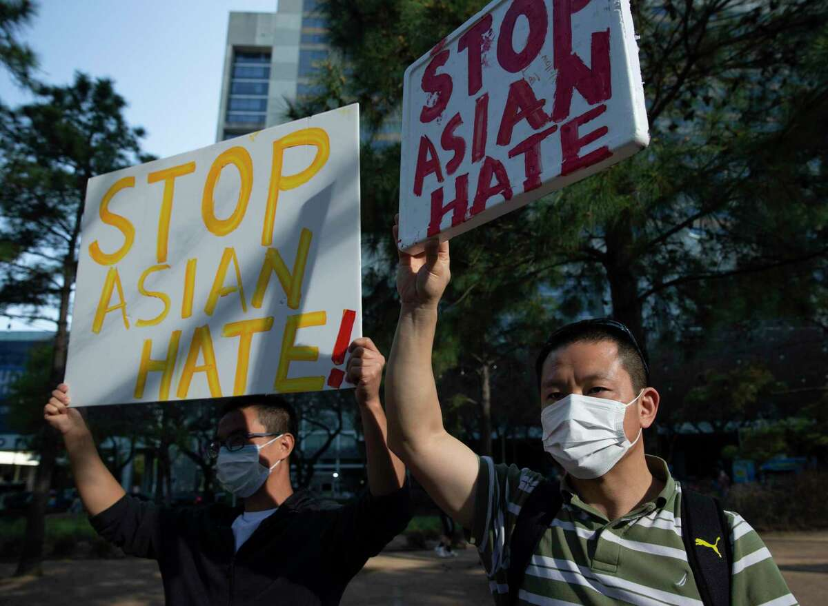 """Allan Lan, right, and Henghua, who wishes not to give his last name, raise signs while participating in a """"Stop Asian Hate Vigil & Rally"""" to mourn the six Asian American victims killed in Atlanta and denounce a rise in hate incidents and violence targeting Asian Americans Saturday, March 20, 2021, at Discovery Green in Houston."""