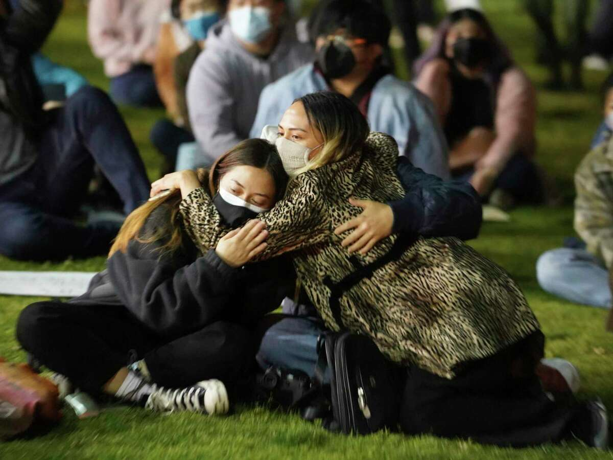 Two participants hug as they join hundreds of people gathered at a candlelight vigil in Alhambra, Calif., Saturday night.