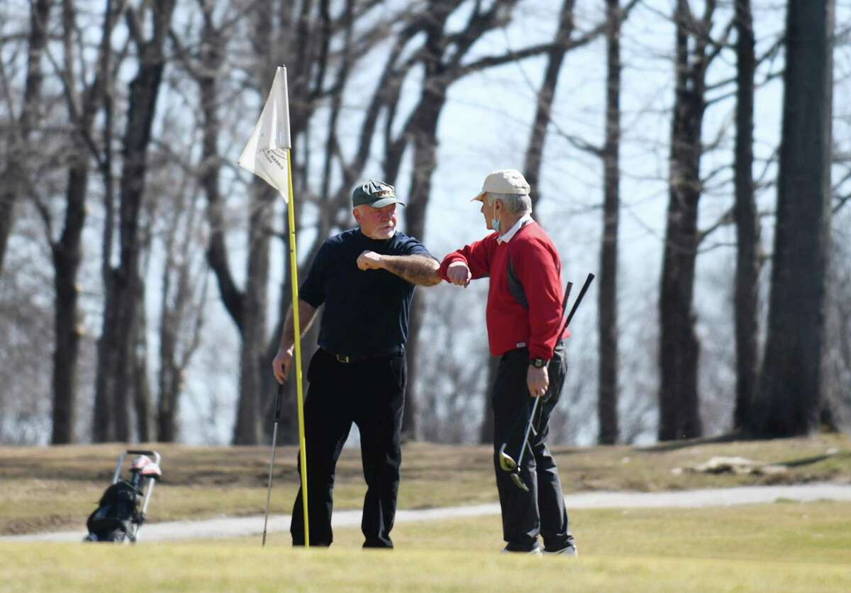 Old Greenwich's Ken Kolb, left, and Cos Cob's Frank DiVincenzo congratulate each other after finishing up a round of golf on the opening day at Griffith E. Harris Golf Course in Greenwich, Conn. Tuesday, March 23, 2021. Greenwich's public golf course opened for the season on Tuesday.