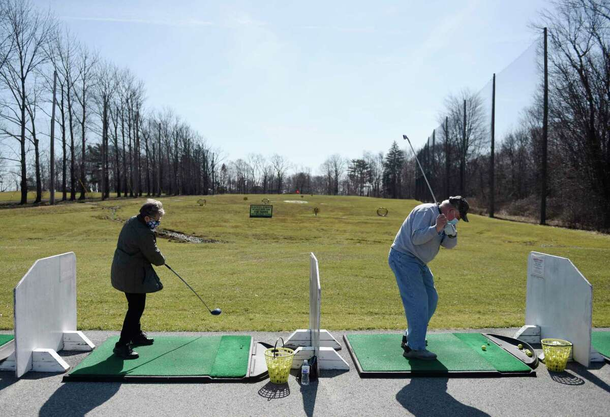 Greenwich's Budy and Gerry Thompson warm up on the driving range on the opening day at Griffith E. Harris Golf Course in Greenwich, Conn. Tuesday, March 23, 2021. Greenwich's public golf course opened for the season on Tuesday.