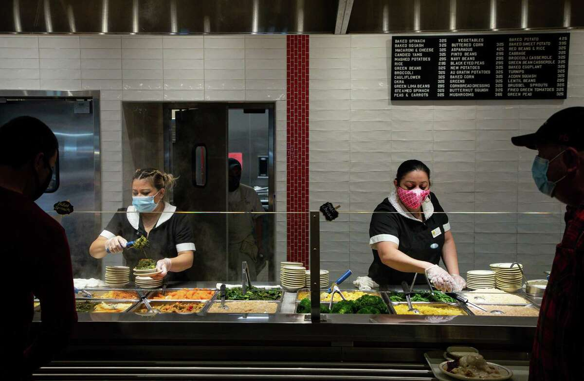 Customers order their food at Cleburne Cafeteria on Thursday, March 18, 2021, in Houston. The restaurant has seen an increase in business by about 20 percent over last month.