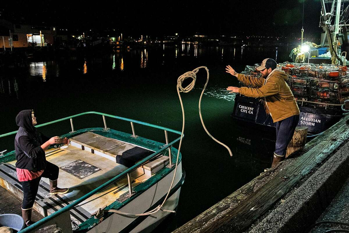 Eight-year deckhand Chris Hofstetter (right) tosses a mooring line to Drake Hoffman aboard the Migrator last week.