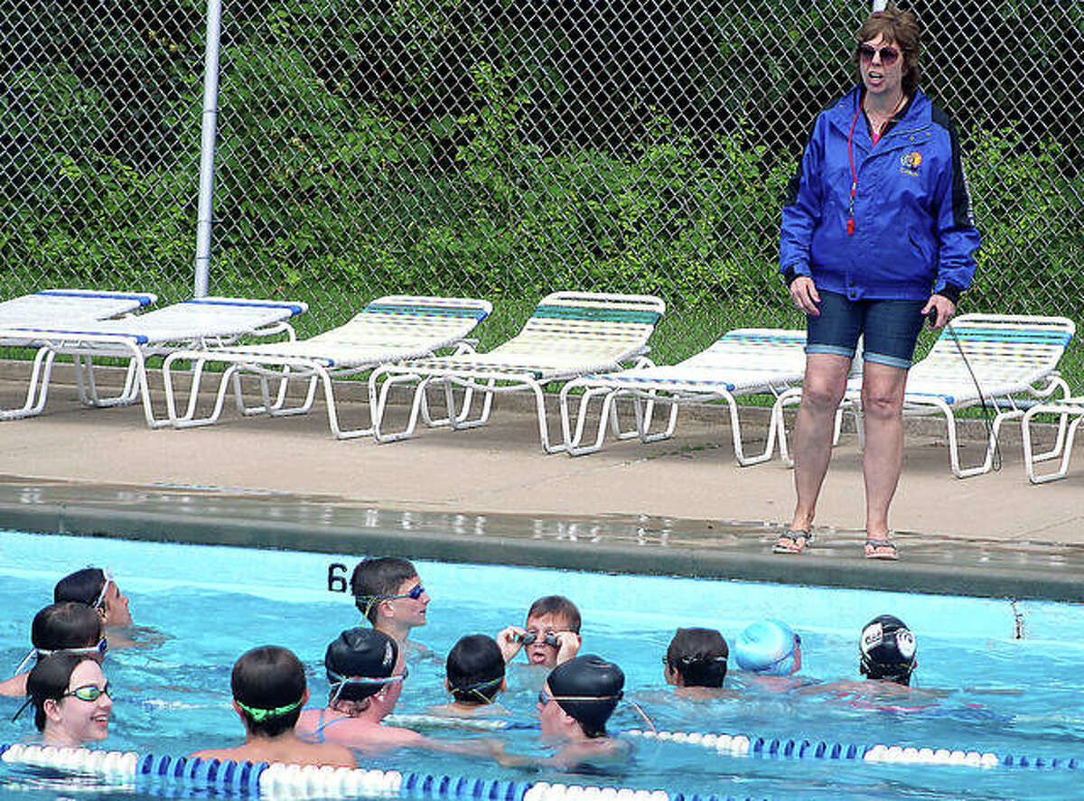 Nancy Miller talks to a group of swimmers at the Summers Port pool in Godfrey. Miller, the longtime TCAY Tidalwaves and Summers Port swim coach, is stepping down.