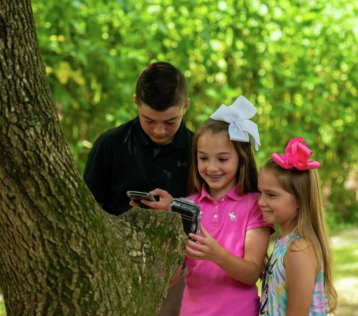 """Ty, Carly and Colbie Cochran use the Geocaching app to find hidden """"caches"""" as part of League City's Geotour."""