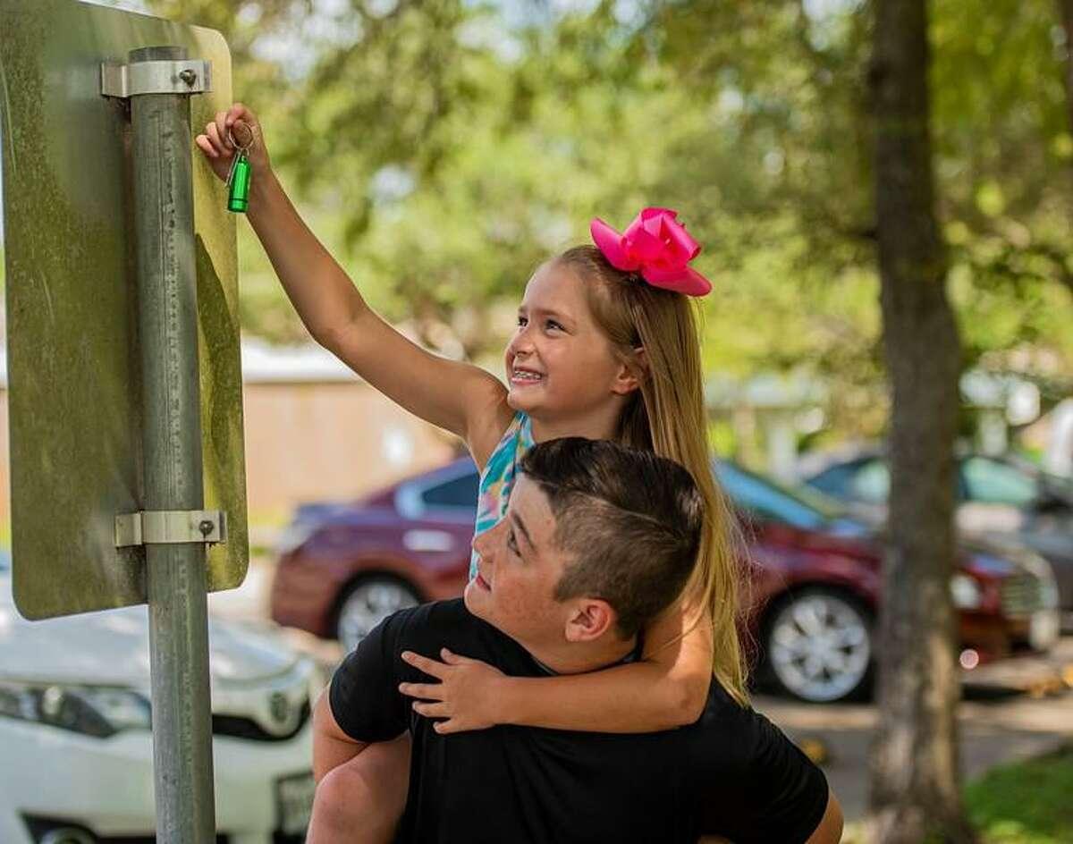 "Ty Cochran helps little sister Colbie find a ""cache"" as part of League City's Geotour."