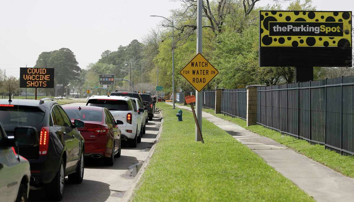 Vehicles line up along Will Clayton Parkway to get into Houston's new vaccination site today at Bush Airport's The Parking Spot location at 5727 Will Clayton Parkway, Tuesday, March 23, 2021.