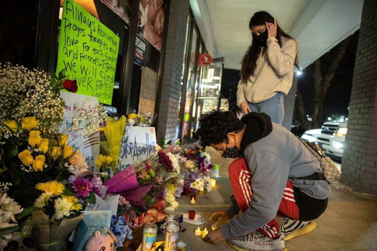 Jeffrey Riso and Cindy Callejas add votive candles to a makeshift memorial outside Young's Asian Massage in Acworth, Ga., which is northwest of Atlanta, March 18, 2021. The nine people shot, eight of whom died, at three spas in the Atlanta area had come from Korea, from China, from Guatemala, from Detroit, and from right up the road in Acworth.