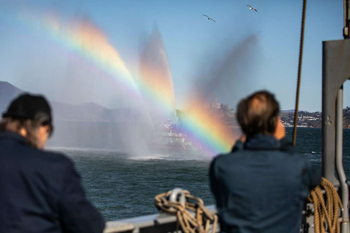 The boat from the S.F. Fire Department gives the Jeremiah O'Brien a water salute during its tow to Pier 45.
