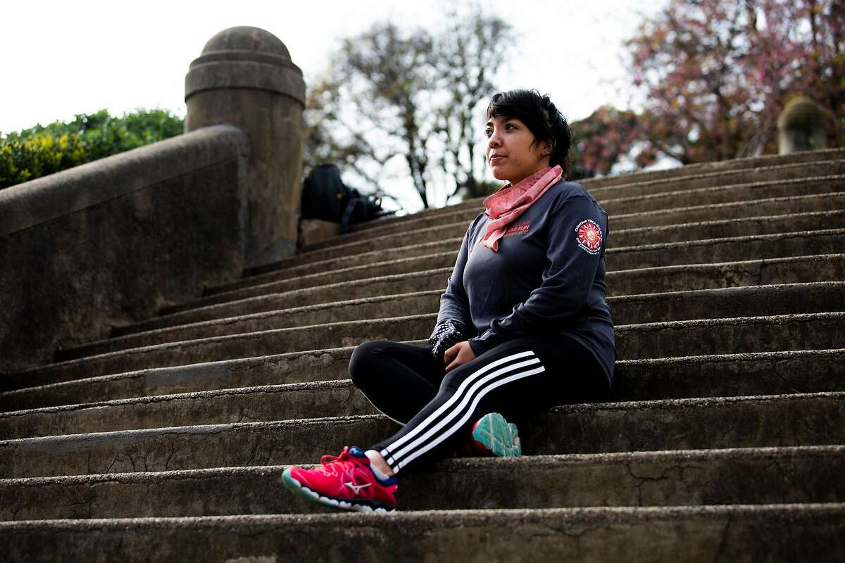 Lizzie Siegle prepares for a run on the stairs at Lafayette Park in San Francisco. While running is an outdoor outlet for her, she says seeing more people out and about can cause her stress.