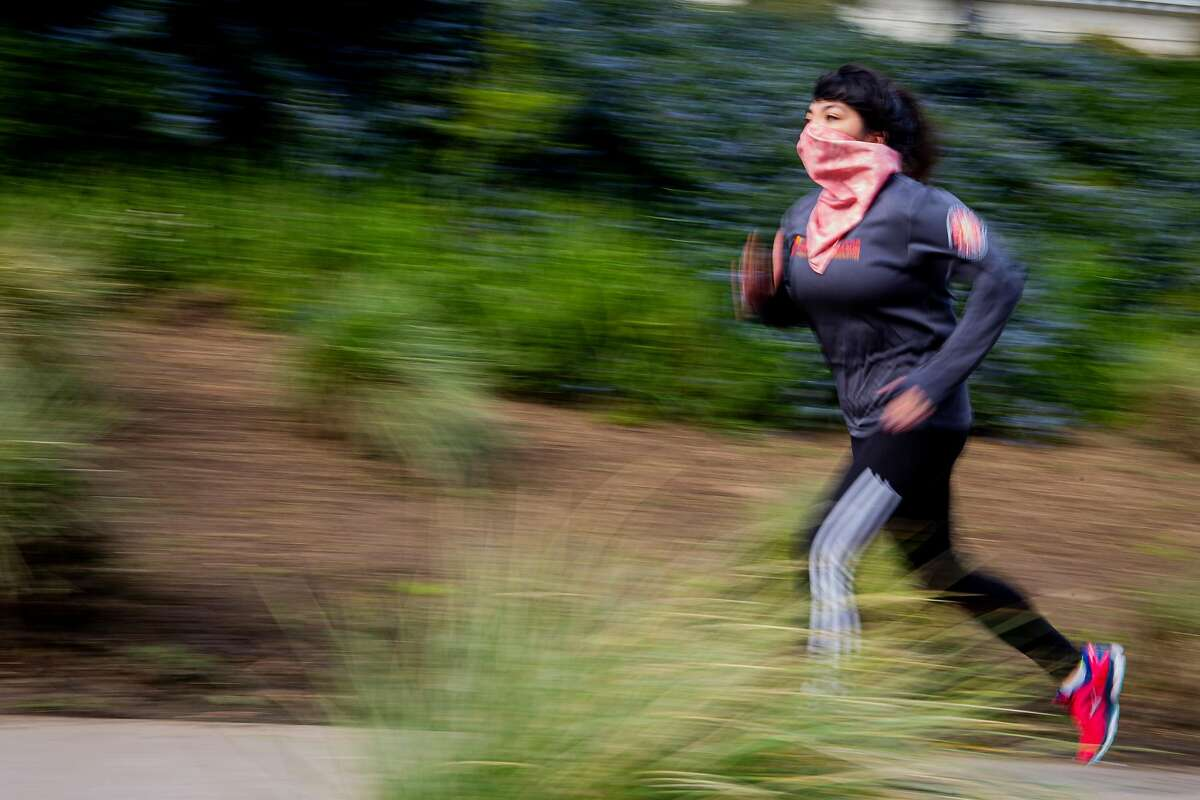 Lizzie Siegle runs up a sidewalk by Lafayette Park in San Francisco. Siegle is anxious about the city's next round of pandemic reopenings and uses running as a means of coping with COVID anxieties.