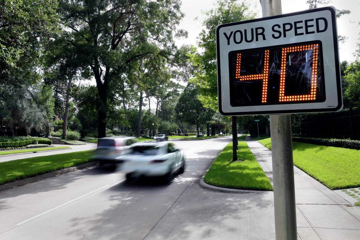 Traffic moves westbound past a speed warning sign in River Oaks along Kirby, just west of Shepherd on July 3, 2020 in Houston.