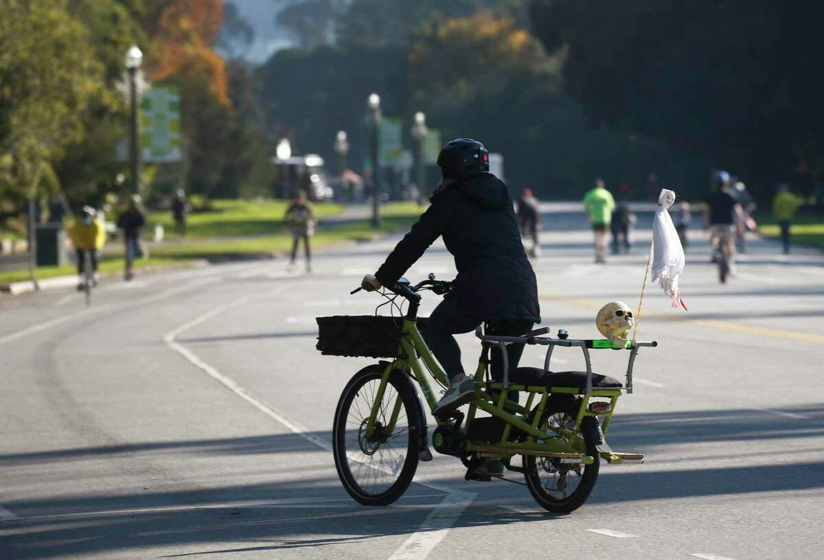 Bicyclists and walkers wear masks and spread out to maintain social distance on JFK Drive, which is closed to thru traffic, at Golden Gate Park in San Francisco, Calif. on Saturday, Nov. 28, 2020.