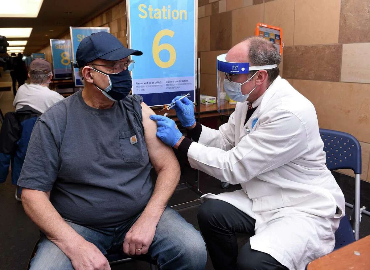 Alan Hurlburt (left) of Cheshire gets his first dose of a COVID-19 vaccine from Dr. Tom Balcezak, chief clinical officer of Yale New Haven Health, at the Floyd Little Athletic Center in New Haven on February 14, 2021. Balcezak and his wife, Dr. Soni Clubb, teamed up to administer COVID-19 injections at the vaccination center for Valentine's Day.