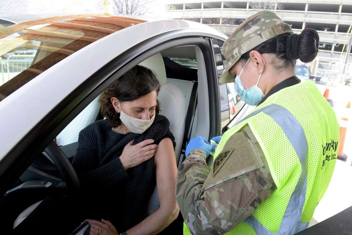 Wilton teacher Lauren Cutler waits to get her vaccination from Connecticut National Guard medic Pfc. Stefanie Charpentier at Danbury's first mass COVID-19 vaccination site at the Danbury Fair mall on March, 4.