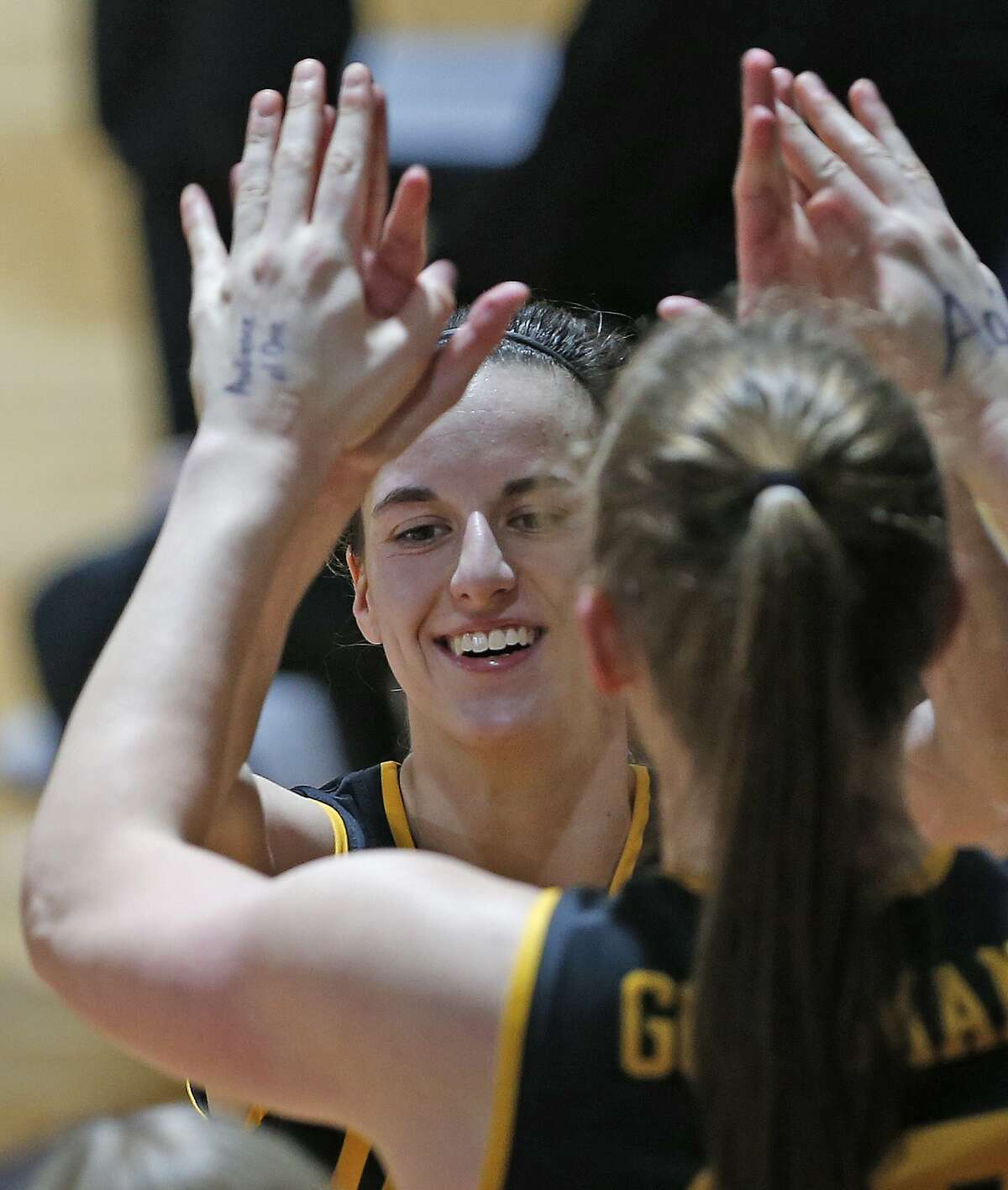 Iowa guard Caitlin Clark (22) receives high fives as she comes to the bench during the second half of a college basketball game in the second round of the women's NCAA tournament at the Greehey Arena in San Antonio, Tuesday, March 23, 2021. Iowa defeated Kentucky 86-72. (AP Photo/Ronald Cortes)