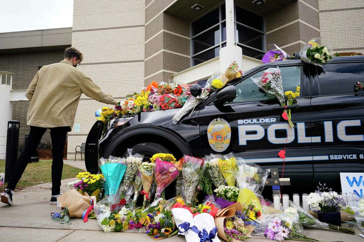 A man leaves a bouquet on a police cruiser parked outside the Boulder Police Department after an officer was one of the victims of a mass shooting at a King Soopers grocery store Tuesday, March 23, 2021, in Boulder, Colo. (AP Photo/David Zalubowski)