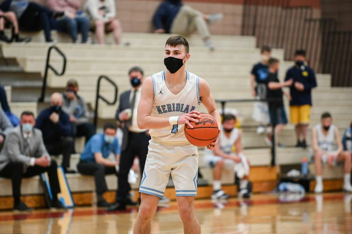 Meridian's Cam Metzger looks to pass the ball during the Mustangs' district quarterfinal game against Beal City Tuesday, March 23, 2021 at Beaverton High School. (Adam Ferman/for the Daily News)