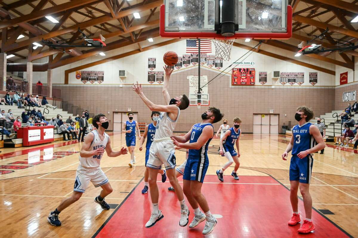 Meridian's Nick Metzger takes a shot under the hoop during the Mustangs' district quarterfinal game against Beal City Tuesday, March 23, 2021 at Beaverton High School. (Adam Ferman/for the Daily News)