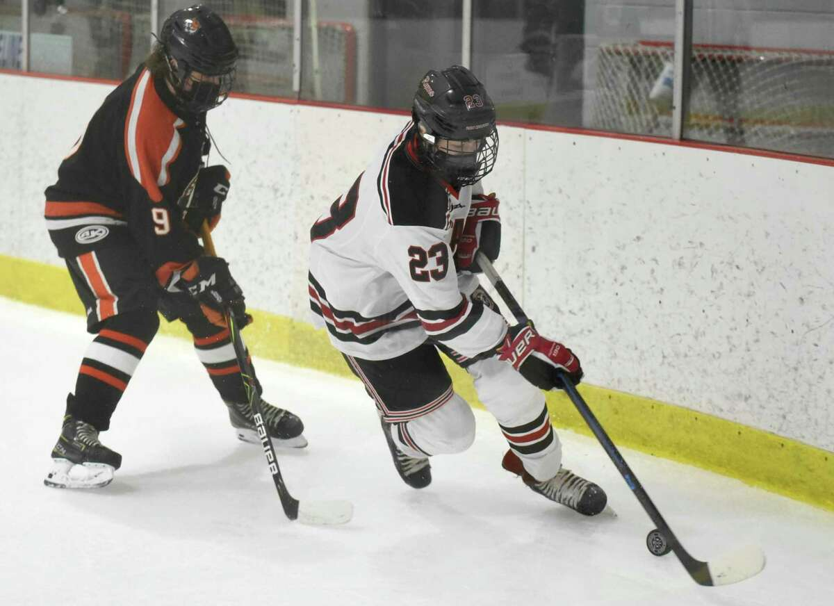 New Canaan's Boden Gammill (23) skates with the puck while Ridgefield's Chris Hamilton (9) pursues during a boys ice hockey game at the Darien Ice House on Saturday, Feb. 13, 2021.