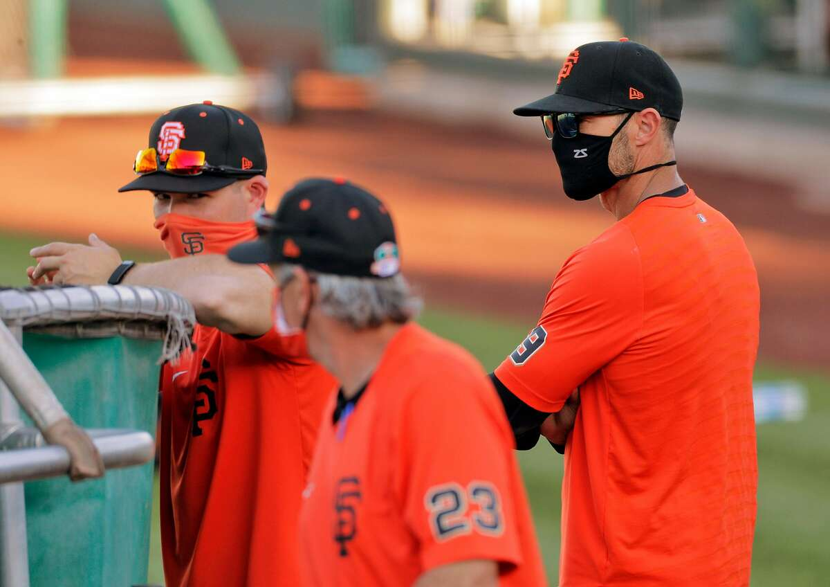 Giants manager Gabe Kapler (right) has coaches who blend old school and new, with Ron Wotus (front) and Dustin Lind (88).