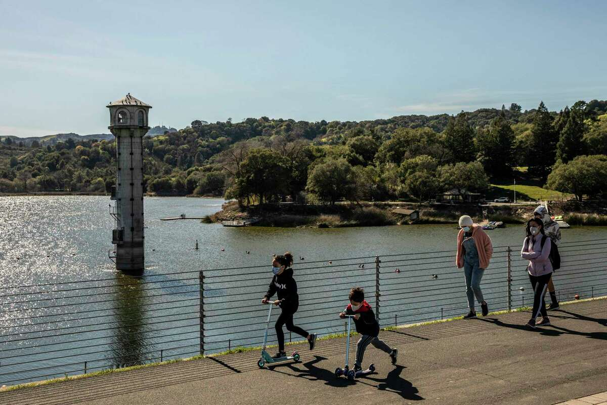 This file photograph shows parkgoers walk and scooter along Lafayette Reservoir in Lafayette, California Sunday, Feb. 28, 2021.