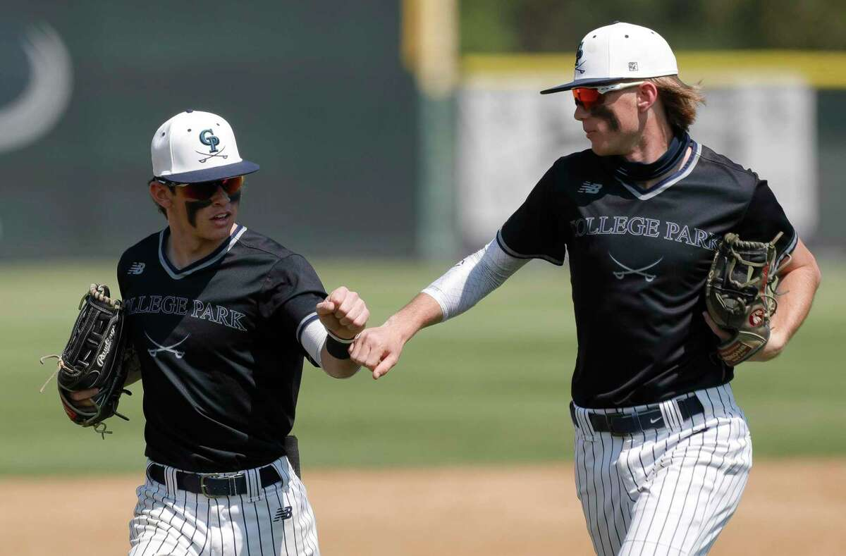 FILE - College Park second baseman Carson Nolen (10) gets a fist-bump from shortstop Garrett Cross (7) after catching a fly ball from Todd Anderson #3 of Conroe to end the top of the fifth inning of a District 13-6A high school baseball game at College Park High School, Friday, March 19, 2021, in The Woodlands.