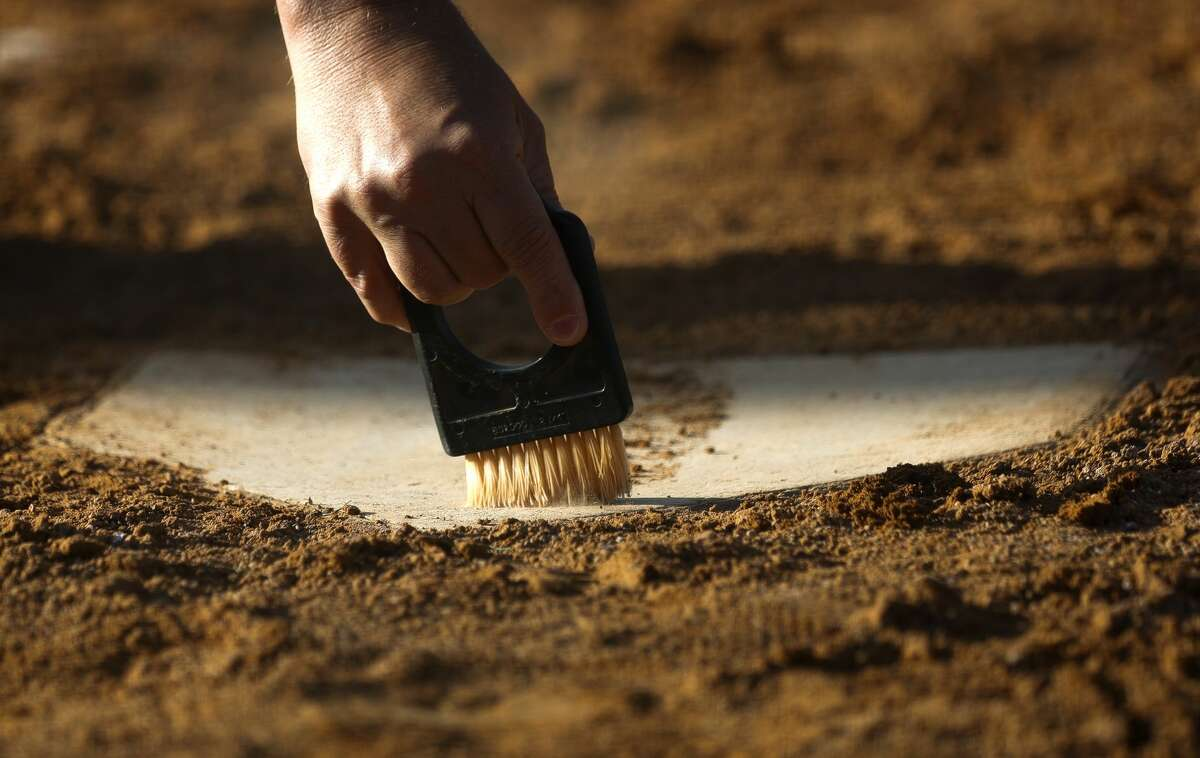 An umpire wipes the dirt off home plate during a District 13-6A high school softball game at Willis High School, Tuesday, March 23, 2021, in Willis