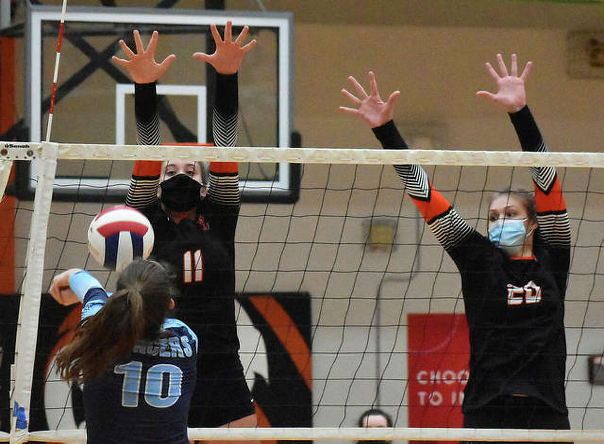 Edwardsville's Gabby Saye, left, and Storm Suhre, right, go up for a block during the first game against Belleville East on Tuesday inside Lucco-Jackson Gymnasium.