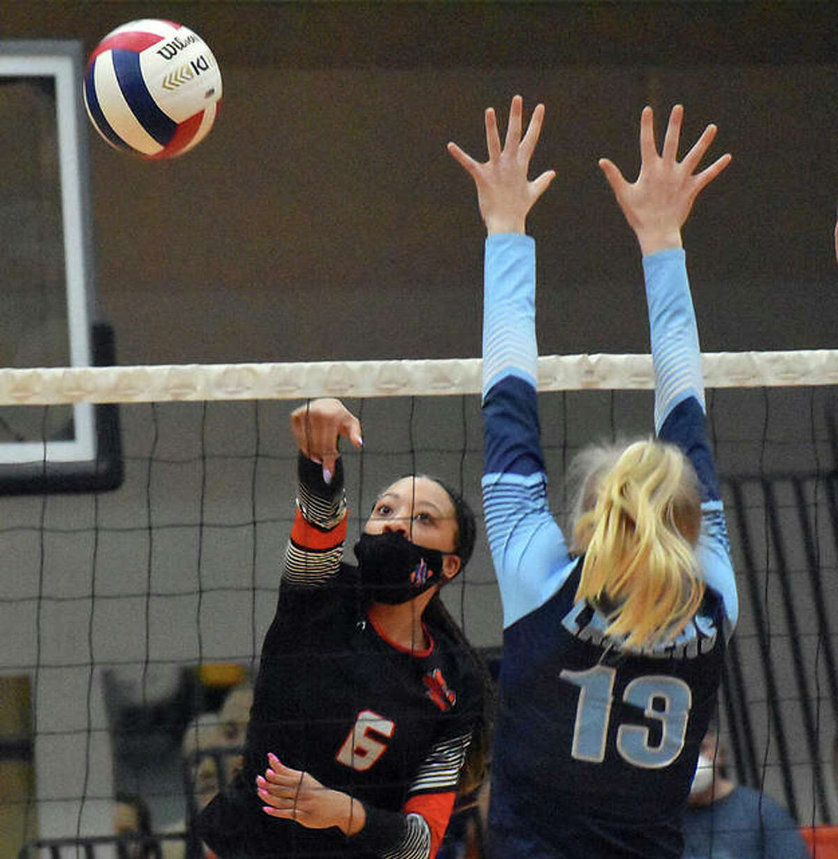 Edwardsville's Alexa Harris slams a kill past a Belleville East blocker during the first game on Tuesday in Edwardsville.