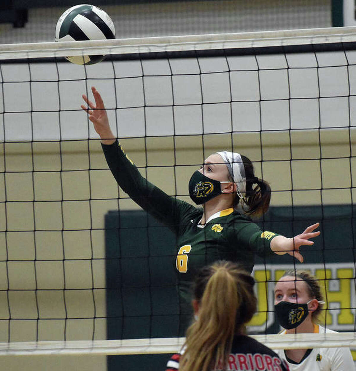 Metro-East Lutheran's Anne Kienle tips a shot over the net in the first game against Granite City.