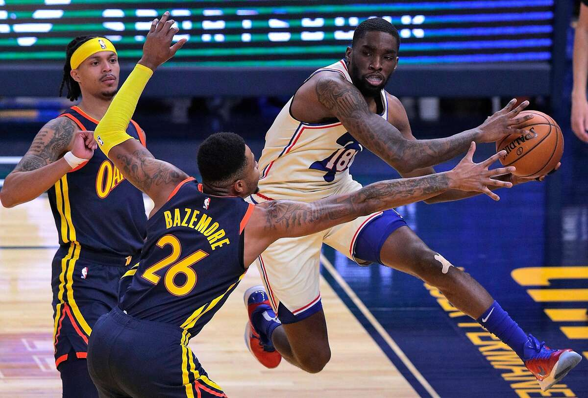 Shake Milton (18) passes defended by Kent Bazemore (26) in the first half as the Golden State Warriors played the Philadelphia 76ers at Chase Center in San Francisco, Calif., on Tuesday, March 23, 2021.