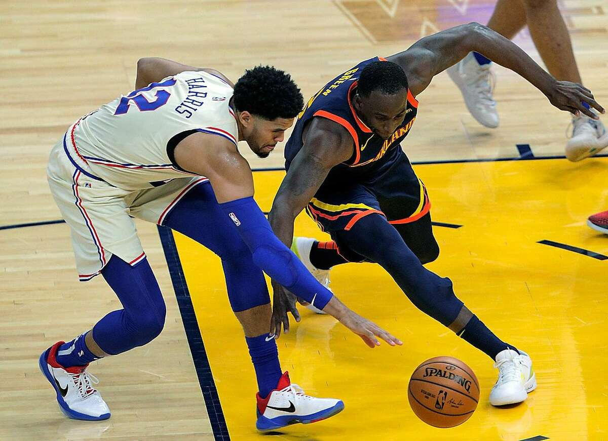 Draymond Green (23) goes for a loose ball against Tobias Harris (12) in the first half as the Golden State Warriors played the Philadelphia 76ers at Chase Center in San Francisco, Calif., on Tuesday, March 23, 2021.