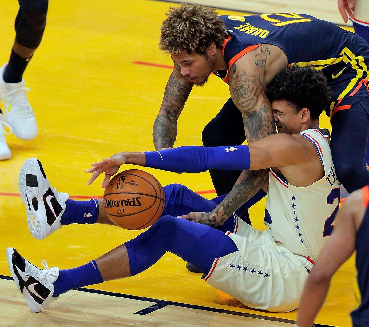 Kelly Oubre Jr. (12) and Matisse Thybull (22) scramble for a loose ball before a jump ball is called in the second half as the Golden State Warriors played the Philadelphia 76ers at Chase Center in San Francisco, Calif., on Tuesday, March 23, 2021.