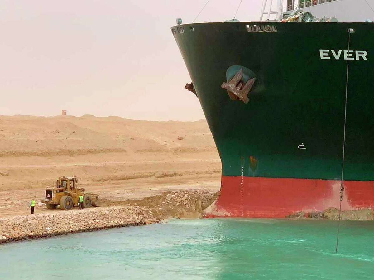 In this photo released by the Suez Canal Authority, a cargo ship, named the Ever Green, sits with its bow stuck into the wall Wednesday, March 24, 2021, after it turned sideways in Egypt's Suez Canal, blocking traffic in a crucial East-West waterway for global shipping. An Egyptian official warned Wednesday it could take at least two days to clear the ship. (Suez Canal Authority via AP)